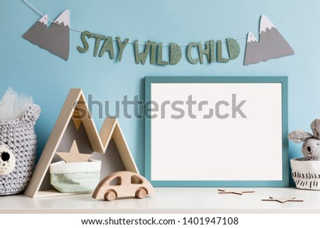 The modern scandinavian newborn baby room with mock up poster frame, wooden toys, mountain box and cotton basket  with children accessories. Cozy interior with blue walls. Hanging stylish inscription