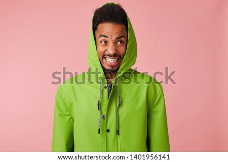 Close up of displeased angry young handsome african american handsome guy in green rain coat , stands over pink background, bursts his teeth aggressively and looks into the camera, looks crazy. #1401956141
