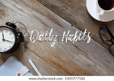 Top view of clock,notebook,pen,glasses and coffee on wooden background written with Daily Habits. #1401977582