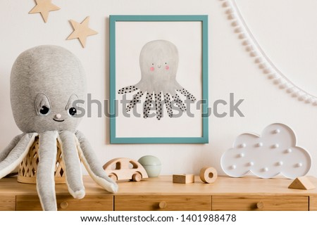 Stylish and cozy child room with white mock up photo frame, wooden accessories, toys, clouds, plush octopus and white garland and stars on the wall. Bright and sunny interior. Template, Real photo.