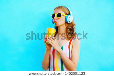 Portrait cool girl drinking fruit juice listening to music in wireless headphones on colorful blue background #1402001123