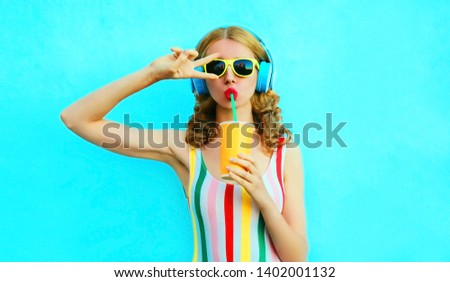 Portrait cool girl drinking fruit juice listening to music in wireless headphones on colorful blue background #1402001132
