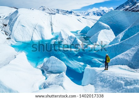 Standing near the edge of large blue pool on top of the Matanuska Glacier. A young woman holding an ice axe with a backpack and helmet looks out over the lake. Royalty-Free Stock Photo #1402017338