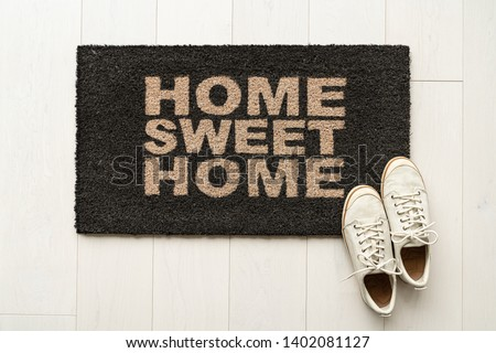 Home sweet home door mat at house entrance with women's sneakers of woman that has just arrived moved in. New condo. Royalty-Free Stock Photo #1402081127