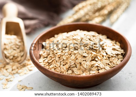 Oat flakes, rolled oats in bowl. Dry breakfast cereals. Healthy eating, healthy lifestyle concept #1402089473