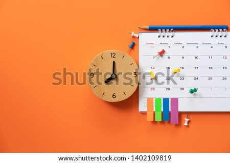 close up of alarm clock and calendar on the orange table background, planning for business meeting or travel planning concept #1402109819