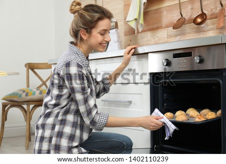 Young woman baking cookies in oven at home #1402110239