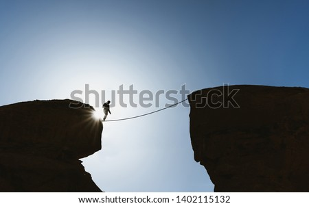 Challenge, risk, concentration and bravery concept. Silhouette a man balance walking on rope over precipice #1402115132