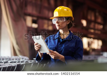 Waist up portrait of female worker using digital tablet while supervising production at plant, copy space #1402116554