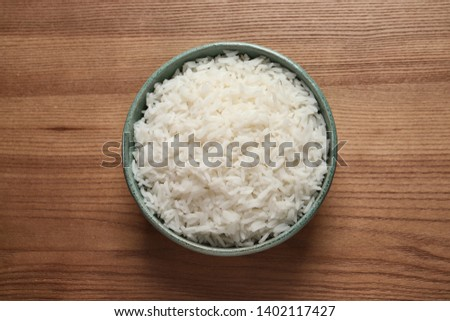 Bowl of cooked rice on wooden background, top view #1402117427