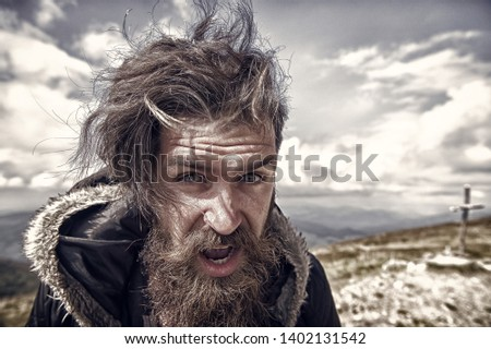 bearded man, long beard, brutal caucasian hipster with moustache on surprised face, unshaven guy with stylish hair getting beards haircut on windy mountain top on natural cloudy sky, copy space #1402131542