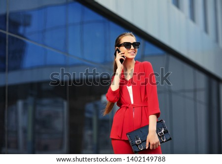 high fashion outdoor Portrait of a young woman in a red pantsuit talking on a mobile phone. Stylish black sunglasses, black clutch, long hair. #1402149788