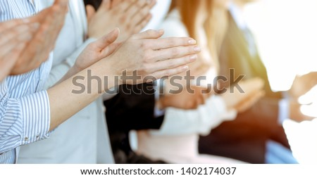 Business people clapping and applause at meeting or conference, close-up of hands. Group of unknown businessmen and women in modern white office. Success teamwork or corporate coaching concept #1402174037