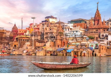 Ancient Varanasi city architecture at sunset with view of sadhu baba enjoying a boat ride on river Ganges. Royalty-Free Stock Photo #1402206599