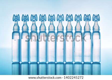 Artificial tears eye drops encapsulated in plastic pipettes and reflected on glass table with blue background. Horizontal composition. Front view #1402245272