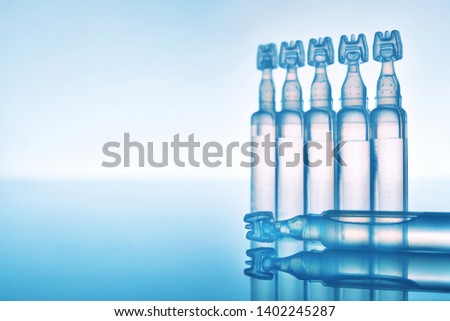 Artificial tears eye drops encapsulated in plastic pipettes and reflected on glass table with blue background. Horizontal composition. Front view #1402245287