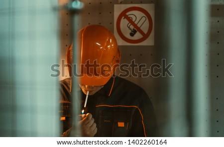 worker smokes near the sign no smoking