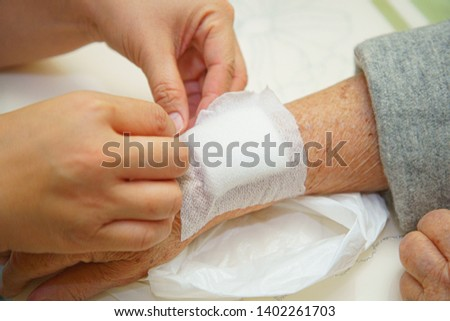 Close up old woman wrinkled skin hand, upper limb or arm to the wounded waiting for nurse treatment on wound dressing a bloody and brine of patient on white background. #1402261703