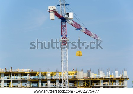 Construction of multi storey residential complex tower cranes in operation. as a rule, equipped with lifting ropes ropes or chains and bundles which can be used both for lifting and lowering materials #1402296497