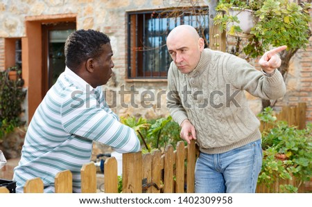 Two displeased male neighbors talking through wooden fence #1402309958