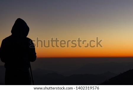 silhouette of Travel photographer standing with a camera mounted on a tripod and shooting a time lapse of the sunrise/sunset. man wearing his hood enjoying the mountain view /valley view #1402319576