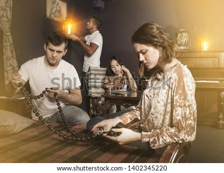 Group of young adults inspecting wooden rosary, trying to find solution of conundrum in escape room with antique furnitures #1402345220