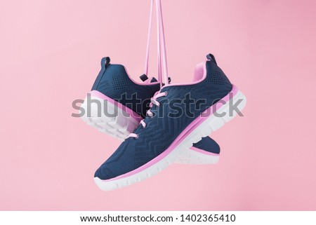 Female sneakers for run on pink background. Fashion stylish sport shoes, close up Royalty-Free Stock Photo #1402365410