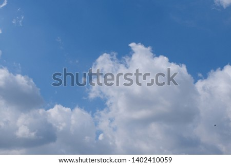 Beautiful bright blue sky with white fluffy clouds on a clear sunny day. Royalty high-quality free stock photo of blue sky with white cloud. Photo of natural cloudscape background