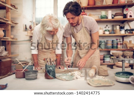 Talented artist. Handsome young man standing near the aged woman while showing her how to paint #1402414775