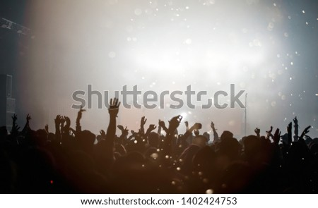 Crowd at concert - Cheering crowd in bright colorful stage lights #1402424753