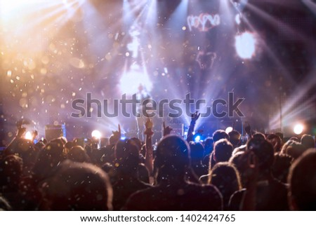 Crowd at concert - Cheering crowd in bright colorful stage lights #1402424765