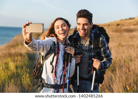 Cheerful young couple carrying backpacks hiking together, walking on a trail, taking a selfie