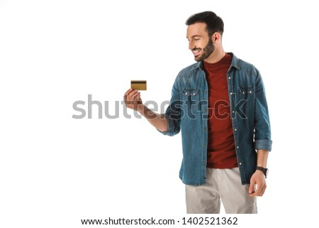 cheerful handsome man in denim shirt holding credit card isolated on white #1402521362