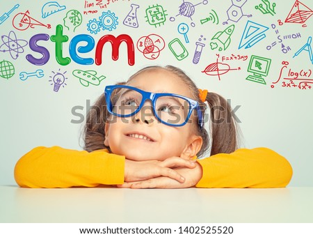 Beautiful cute little girl with eyeglasses looking at colorful STEM word and symbols above her head.  E-learning, modern and innovative Stem education concept. #1402525520