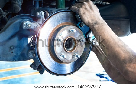 Disk brake and car disk brake system service concept - Car disk brake pad replacement service by hand of mechanic man in car garage with flare light effect and copy space #1402567616