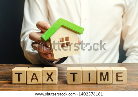 Wooden blocks with the word Tax time and a miniature house in the hands of a businessman. The concept of paying tax for housing and property. Debt payment. Property taxes. Mortgage #1402576181