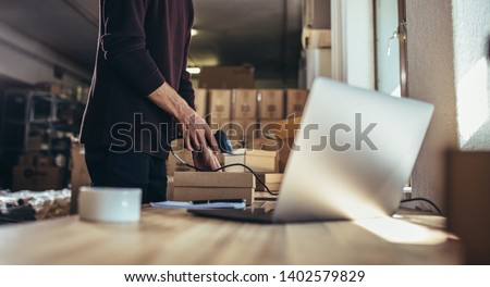Cropped shot of man scanning the barcode of the shipment at his desk. Man working in a drop shipping office, preparing a parcel to deliver to the customer. #1402579829