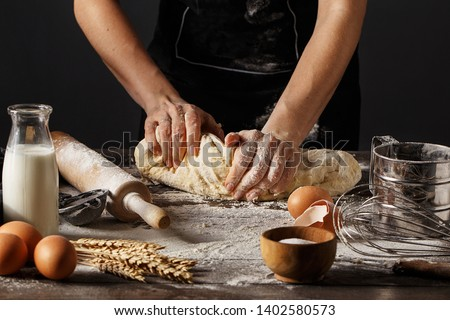 Woman in black apron kneading dough on wooden table with spelt flour, raw eggs, bottle with milk, rolling pin and wheat spikes. Step by step recipe of cooking dough, bakery products or pastry Royalty-Free Stock Photo #1402580573