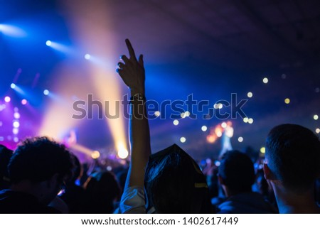 crowd at the concert with background lights, hands in the air and filming with mobile phones #1402617449