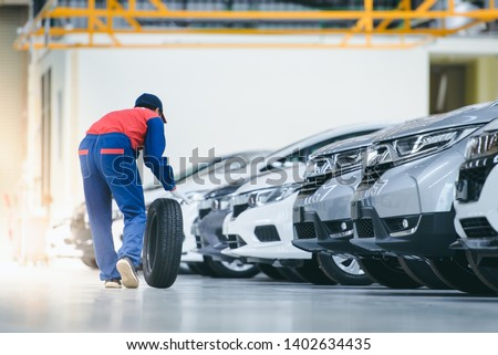 The mechanic is holding a car tire to change tires at the car garage in the work area which is the epoxy floor. In a car repair shop or service center Changing tires before the rainy season arrives #1402634435