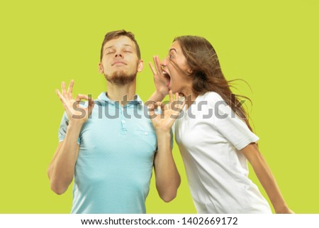 Beautiful young couple's half-length portrait isolated on green studio background. Man is trying to keep calm with closed eyes while woman is screaming. Facial expression, human emotions concept.