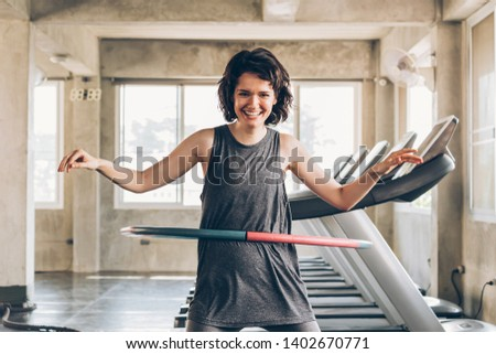 Beautiful young smiling happy Caucasian sporty woman with short hair playing hula hoop inside gym studio with treadmills behind - fun workout fitness portrait concept Royalty-Free Stock Photo #1402670771