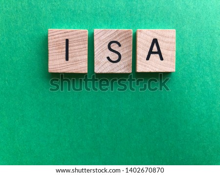 ISA / acronym for Individual Savings Account, in wooden alphabet letters on a plain green background with copy space. Creative concept, banking and finance #1402670870