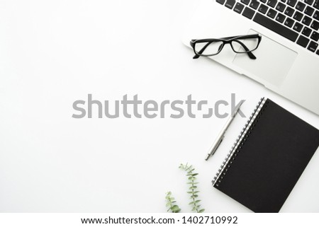 White minimalist office desk table with laptop computer, notebook with pen and eye glasses. Top view with copy space, flat lay minimal style. #1402710992
