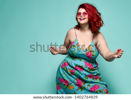 Lucky plus-size lady overweight woman in fashion sunglasses and colorful sundress happy dancing, celebrating on mint background with free text space #1402764839