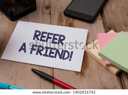Word writing text Refer A Friend. Business concept for direct someone to another or send him something like gift Top view wooden table stationary paper tablet pen colored stick pad notes. #1402816742