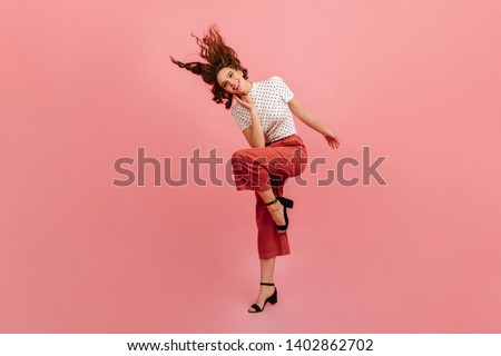 Glamorous woman in black shoes dancing with smile. Studio shot of laughing cute girl in pink pants. #1402862702