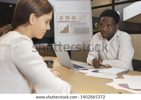 Attractive dark skinned male recruiter interviewing nervous young Caucasian female and making notes in curriculum vitae. Human resources, job, career and employment concept. Selective focus #1402865372