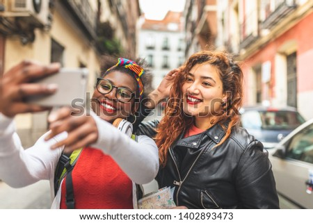 Two Female Friends Taking a Selfie Outdoors. Afro American and Latin Girl Having Fun in the Street. Red Hair Girl Hanging out with Afro american Friend. Youth Concept. #1402893473