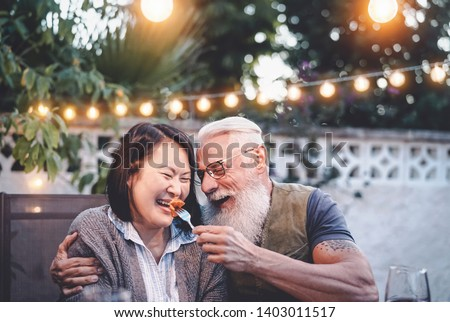 Happy senior couple having fun at dinner house party - Older people with different ethnicity doing a romantic date for celebrating anniversary - Elderly, food, drink and love concept #1403011517